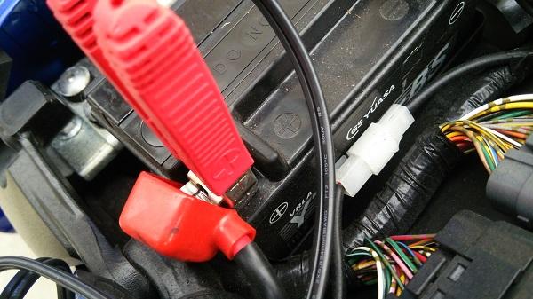 充電器のクリップをバッテリーの端子に接続した様子