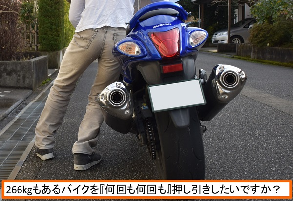 人間がバイクを押している様子