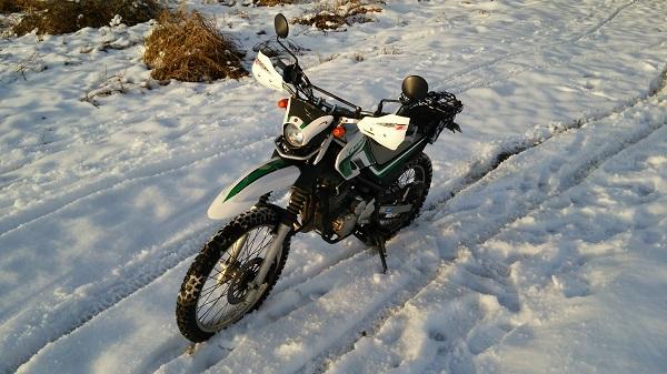 ヤマハのオフロードバイクのセロー250が雪の積もった河川敷に停まっている様子