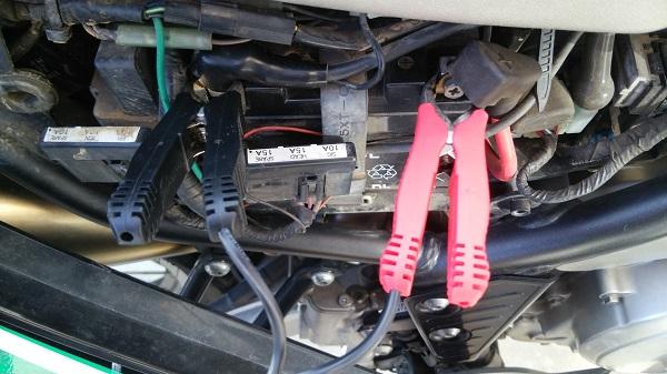ヤマハのオフロードバイクのセロー250のバッテリーの端子に充電器のクリップを接続する様子