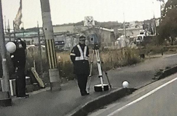 歩道に立っている人と速度計測器