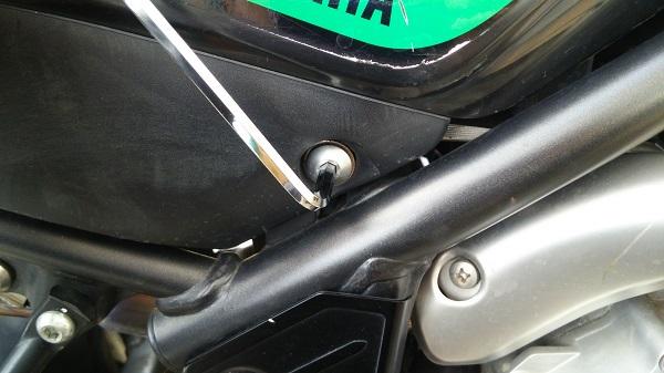 ヤマハのオフロードバイクのセロー250のカバーを締結しているボルトを六角レンチで緩めている様子