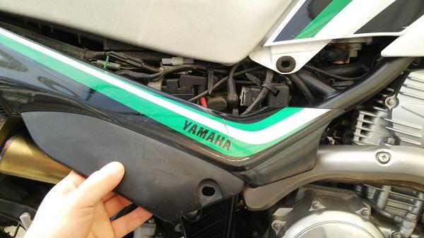 ヤマハのオフロードバイクのセロー250のカバーを手で外している様子