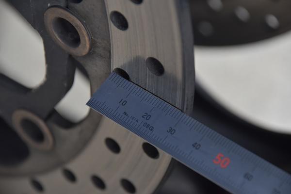 バイクのディスクローターをスケールで測っている様子