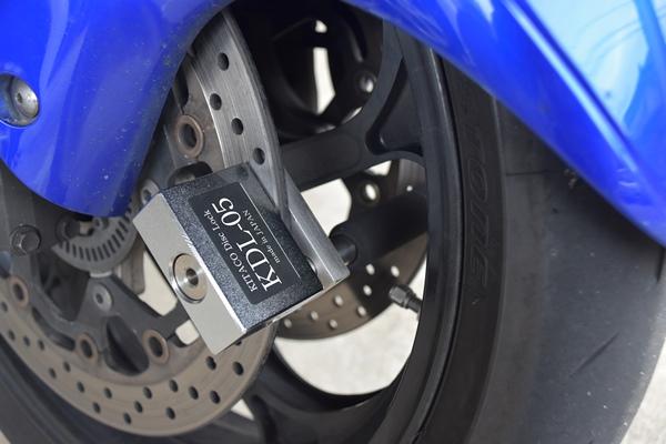 キタコのディスクロックのKDL-05をバイクのディスクローターに取り付ける様子