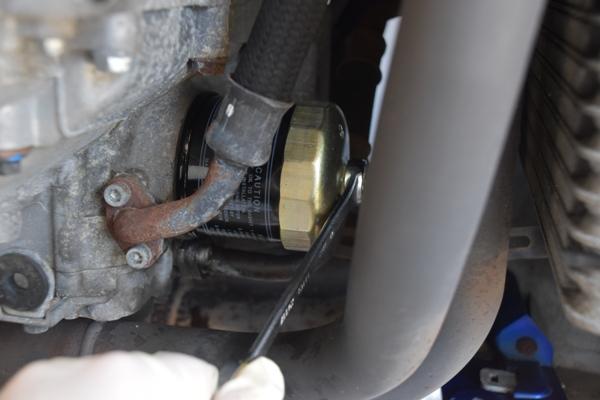 バイク エンジン オイルフィルターをレンチで外す様子