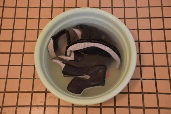 バイクのヘルメットの内装を洗剤を混ぜた水で洗う様子
