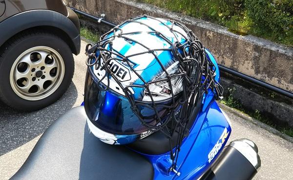 バイクのヘルメットがネットフックで固定されている様子