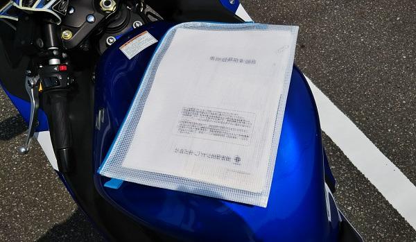 ユーザー車検 クリアファイルがバイクのタンクの上に置かれている様子